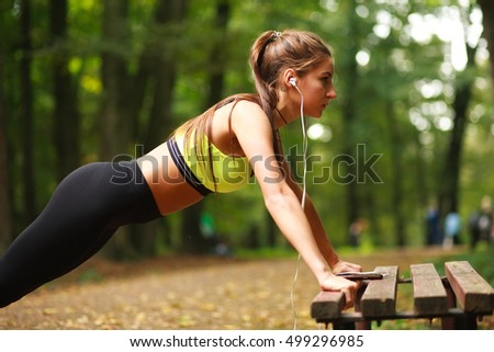 Young woman with headphones doing push-ups exercises in a summer park