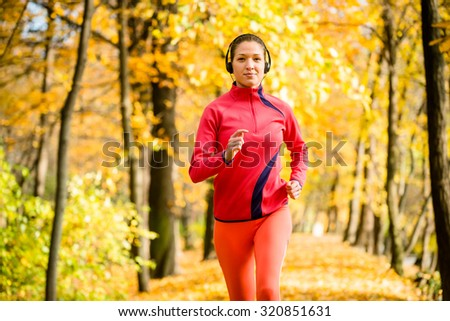Young woman with headphones  jogging in autumn nature and listening music - stock photo
