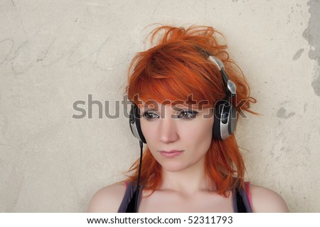 Young woman with headphones posing on a vintage background