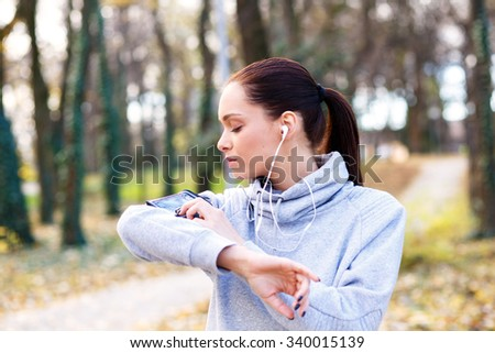 Young woman with headphones preparing for a jogging in autumn park, she is to mobile phone.