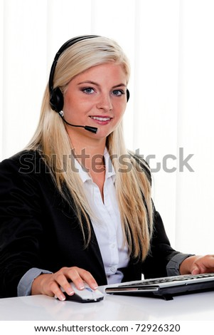 Young woman with headset at computer hotline. Friendly Clerk