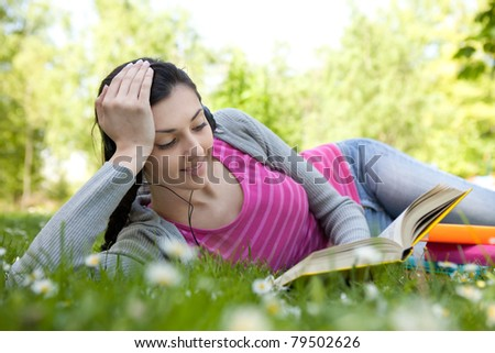 young woman with headset listening music and reading book in park, lying on grass
