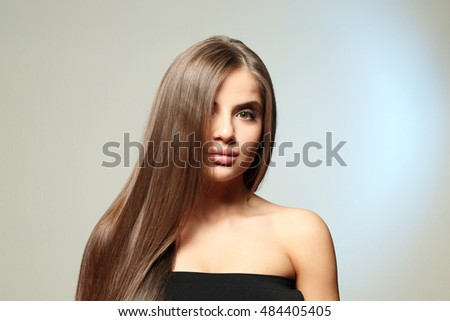 Young woman with healthy hair on light background