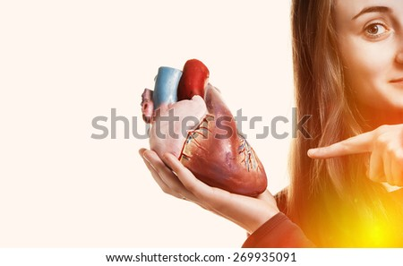 Young woman with heart in hand. Abstract creative background. With copy-space