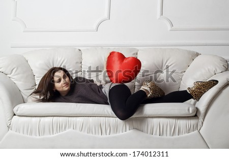 Young woman with heart on the sofa - stock photo