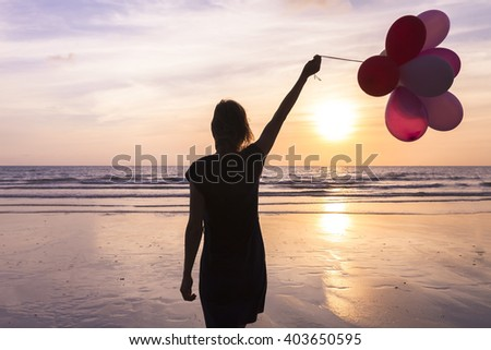 Young woman with helium balloons in hand walking on the beach at sunset, concept about birthday and happy events - stock photo