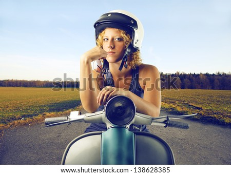 young woman with helmet on the scooter - stock photo