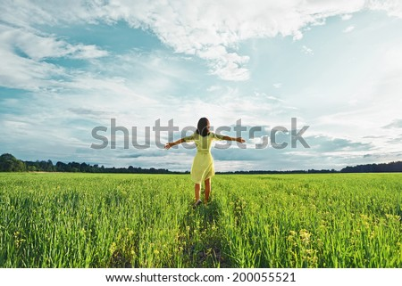 Young woman with her arms wide spread is enjoying in the sunny summer day, rear view - stock photo