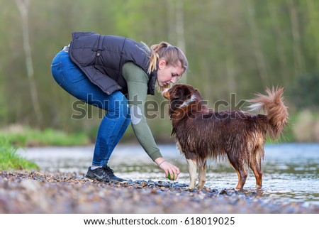 young woman with her Australian Shepherd dog at the river
