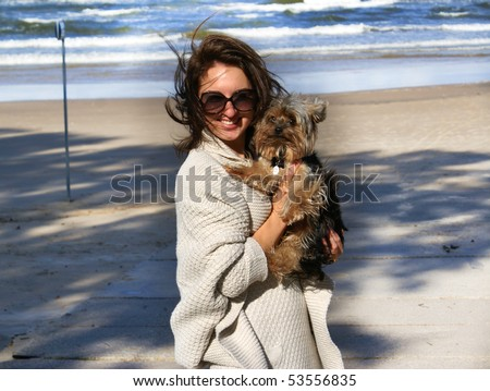 Young woman with her beautiful dog at the baltic beach - stock photo