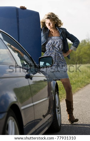 Young woman with her broken car looking at car engine