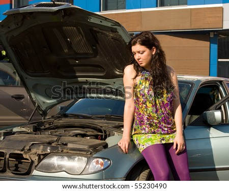 Young woman with her broken car. The girl is sad. Vehicle Breakdown. Beautiful girl thinking about what to do with car breakdown - stock photo