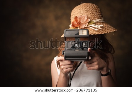 Young woman with her camera on a old background - stock photo