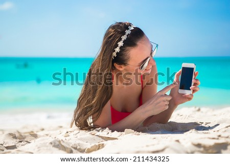 Young woman with her cell phone on white beach - stock photo