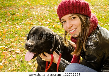 young woman with her dog in park - stock photo