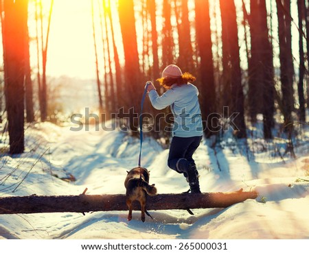 Young woman with her dog jumping over a log in snowy winter - stock photo