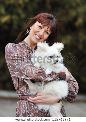 Young woman with her dog outdoors - stock photo