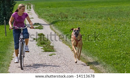 young woman with her dog running beside her - stock photo