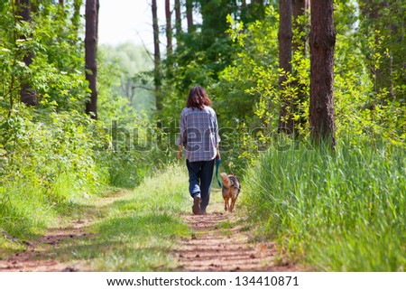 Young woman with her dog walking in the forest - stock photo