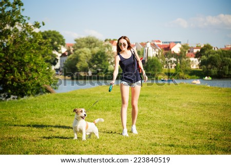 Young Woman with her Dog Walking in the Park. Healthy Lifestyle Concept. - stock photo