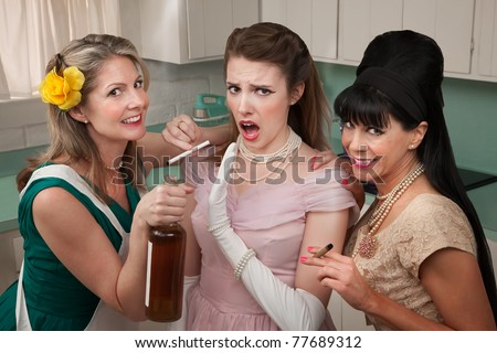 Young woman with her friends smoking and drinking in the kitchen - stock photo