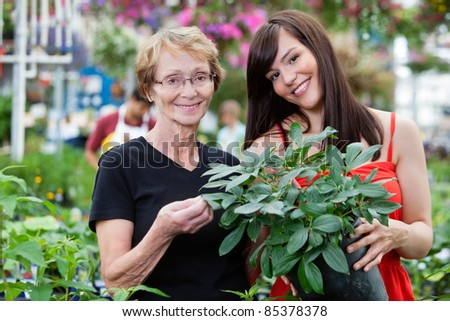 Young woman with her grandmother holding potted plant with people in background