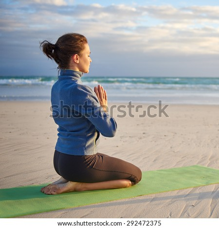 Young woman with her hands together kneeling on her yoga-mat doing some meditation and breathing exercises on the beach early in the morning - stock photo