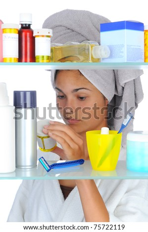 Young woman with her head wrapped in a towel looking at prescription bottle in front of bathroom Medicine Cabinet. Vertical format isolated on white.
