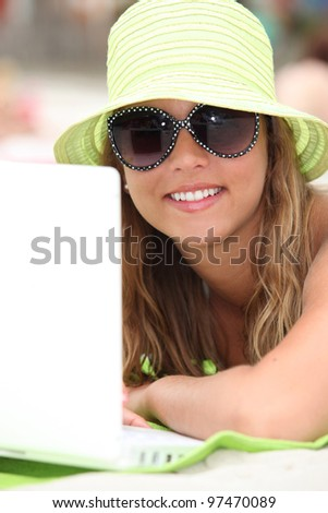 Young woman with her laptop at the beach