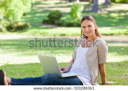 Young woman with her laptop sitting on the lawn