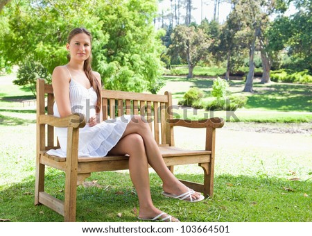 Young woman with her legs crossed sitting on a park bench - stock photo