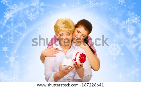 Young woman with her mother on blue winter background - stock photo