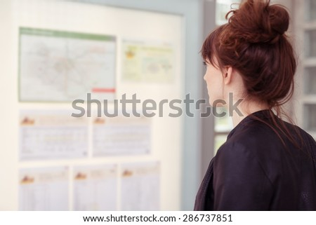 Young woman with her red hair in a bun standing reading notices on a bulletin board indoors, profile view from behind - stock photo