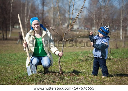 young woman with her son planting the tree outdoor - stock photo