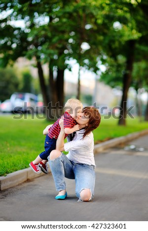 Young woman with her toddler son having fun outdoors  - stock photo
