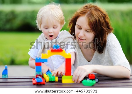 Young woman with her toddler son playing with colorful plastic blocks outdoors - stock photo