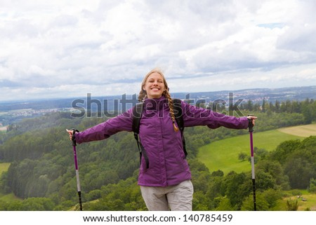 Young woman with hiking sticks top of the mountain - stock photo
