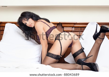 Young woman with hot sexy body in bed - stock photo