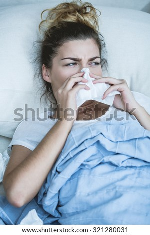 Young woman with influenza lying in bed - stock photo