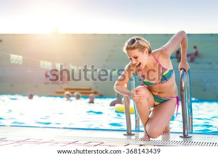 Young woman with injured leg at the swimming pool - stock photo