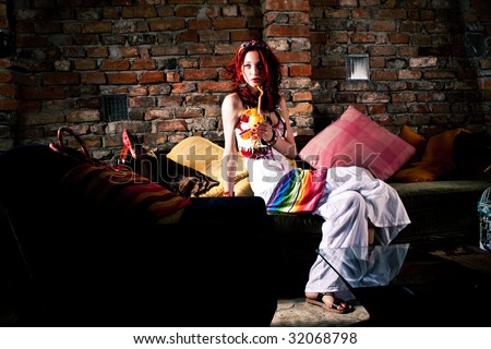 young woman with juice by brick wall - stock photo