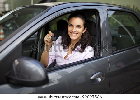 Young woman with keys in a car - stock photo