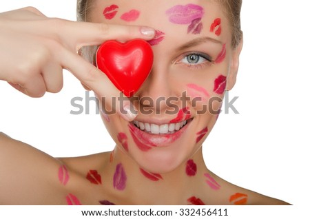 young woman with kisses on face holding heart eyes isolated on white