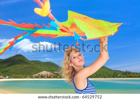 Young woman with kite on the beach - stock photo