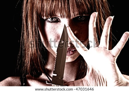 Young woman with knife on black background - stock photo