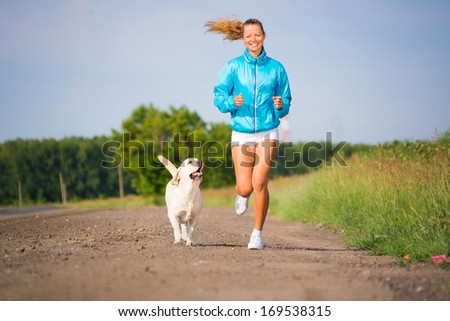 young woman with labrador running on a country road, outdoor training - stock photo
