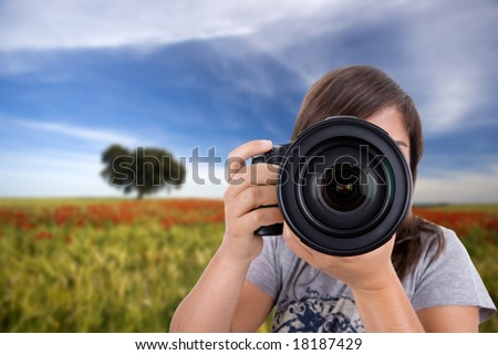 young woman with landscape as background taking photos - stock photo