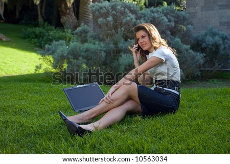 young woman with laptop and phone working at outdoor