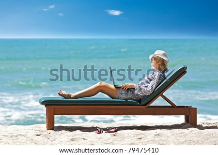 Young woman with laptop at the tropical beach - stock photo