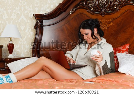 Young woman with laptop lies on the house bed.
